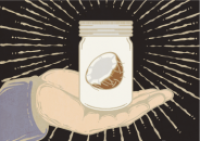 A mason jar containing half of a coconut held in the palm of an open hand