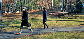 Two people walking outdoors at the MIT Lincoln Labs facility grounds