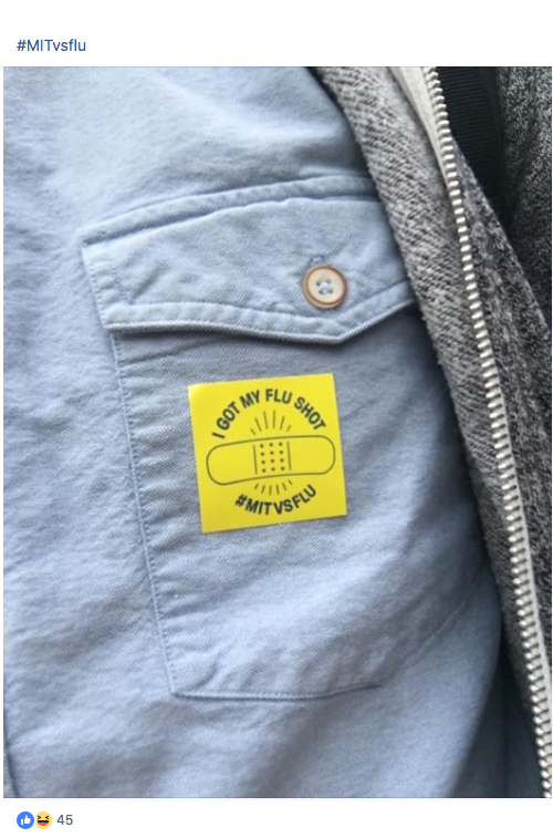 "Closeup of a person's shirt front with a yellow sticker on the pocket that reads ""I got my flu shot. #MITvsFLU"""