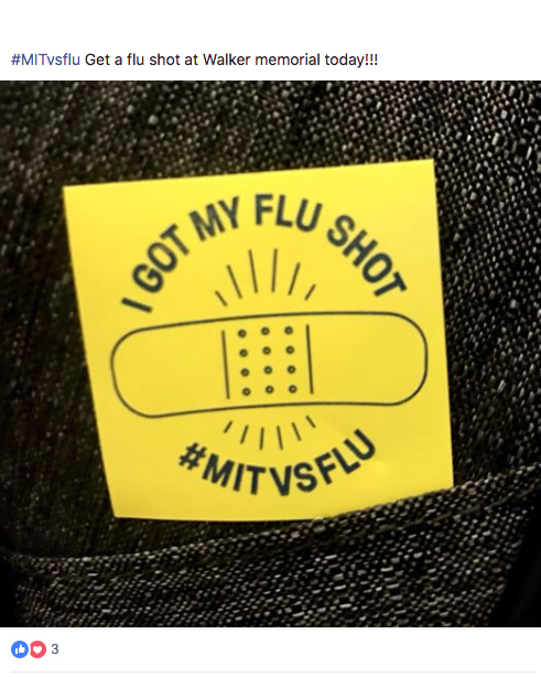 "Closeup of a person's sweater with a yellow sticker on the front that reads ""I got my flu shot. #MITvsFLU"""