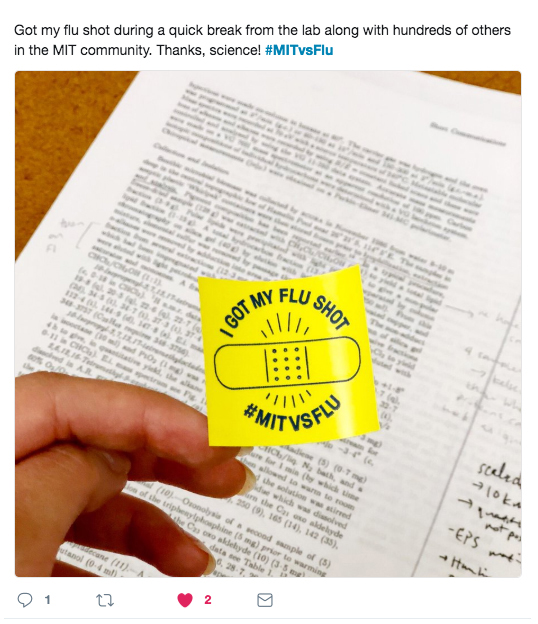 "Hand holding a yellow sticker that reads ""I got my flu shot. #MITvsFLU"""
