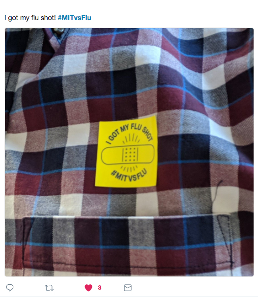 "Closeup of a person's shirt front with a yellow sticker above the pocket that reads ""I got my flu shot. #MITvsFLU"""