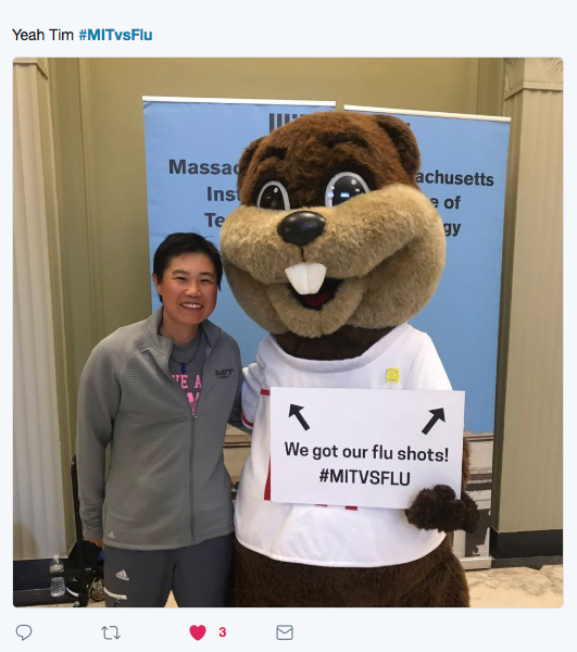 "Smiling person posing with Tim the Beaver who is holding a sign that reads ""We got our flu shots! #MITvsFlu"""