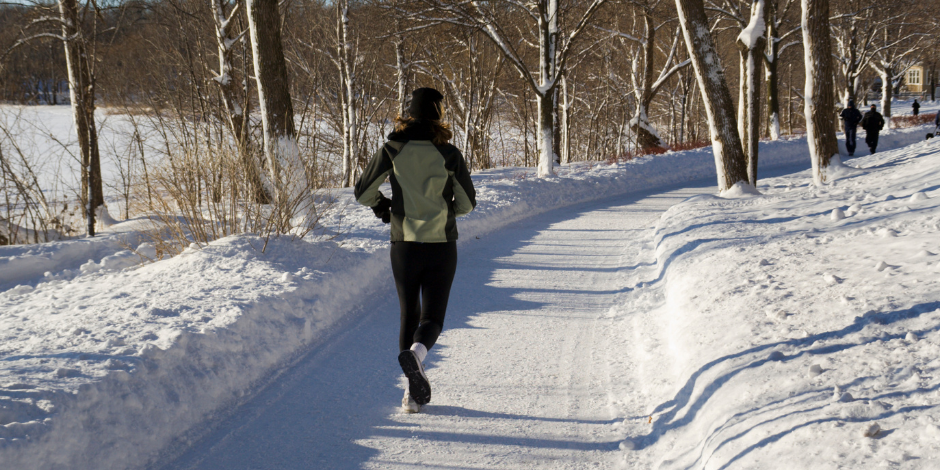 """""""view of person jogging on a snowy path next to a pond"""""""
