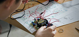 Student sitting at a table working on an electronic unit